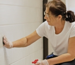 custodian cleaning a wall