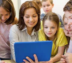 teacher with students looking at a tablet